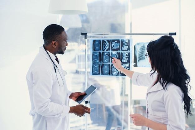 Два доктора смотрят на рентген и обсуждают проблему. медицинские техники, указывая на мрт рентгеновского пациента. радиолог проверяет рентген. медицинская и радиологическая концепция.