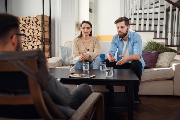 Досадно, кавказская пара мужчина и женщина, разговор с психологом на сеанс терапии в светлой комнате.