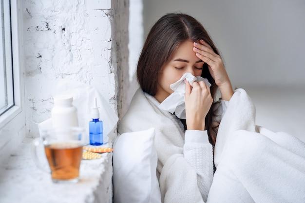 病気の女性が風邪をひいた、病気を感じ、紙拭きでくしゃみをする