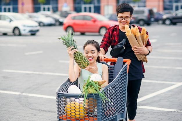 ハンサムなベトナム人男性は、彼の幸せな美しいガールフレンドと一緒にショッピングトロリーの前で食べ物を押しながら紙袋を押します。面白い家族の買い物。