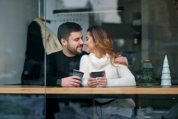 愛の美しい白人カップルは、カフェでコーヒーを飲みます。愛とロマンチック。