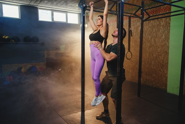 Красивая сильная мышечная женщина делает тянуть вверх упражнения с помощью личного тренера это тренажерный зал.