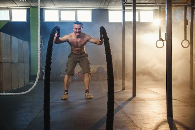 Красивый сильный человек, делать упражнения для мышц с битвы веревки в фитнес-зал.