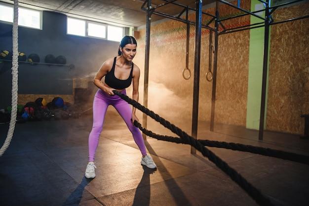 Кавказская спортивная женщина, тренирующаяся с веревками в спортзале.
