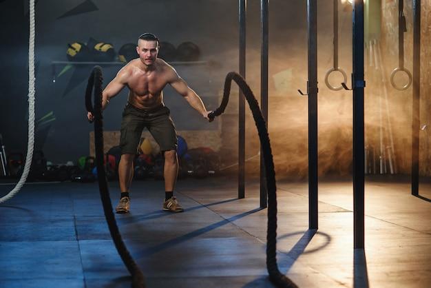 Молодой спортивный человек делает упражнения с битвы веревки в фитнес-зал.