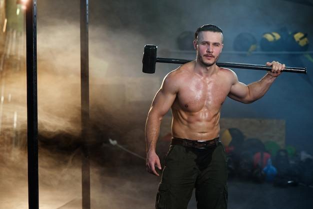 肩にハンマーで強い筋肉の男。