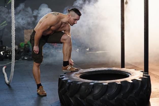 裸の胴体を持つ筋肉の男は、ジムで重いタイヤの近くに残りを持っています。