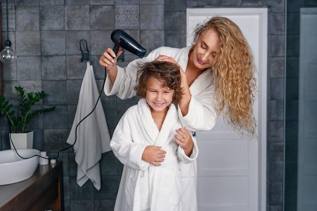 美しい母は白いバスローブに身を包んだ彼女の小さな幸せな息子にドライヤーで髪を乾かします。