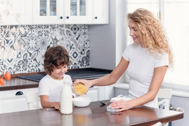 Красивая мама готовит здоровый завтрак из кукурузных хлопьев и молока для любимого сына.
