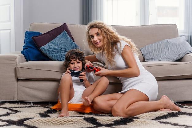 Молодая женщина, играя в видеоигры с сыном дома