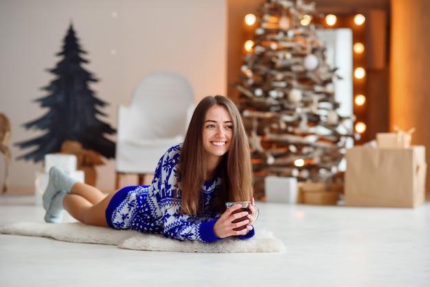 Привлекательная милая девушка в вязаном праздничном свитере лежит на белом ковре