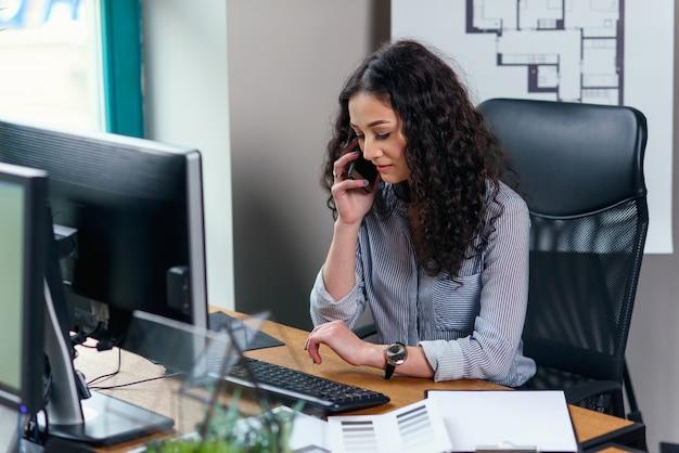 Молодой женский дизайнер интерьера говорит на смартфоне и смотрит на часы во время рабочего дня в современном офисе.