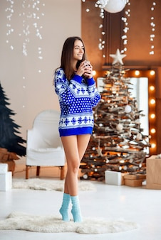 Красивая девушка в теплый праздничный свитер с чашкой теплого чая с корицей