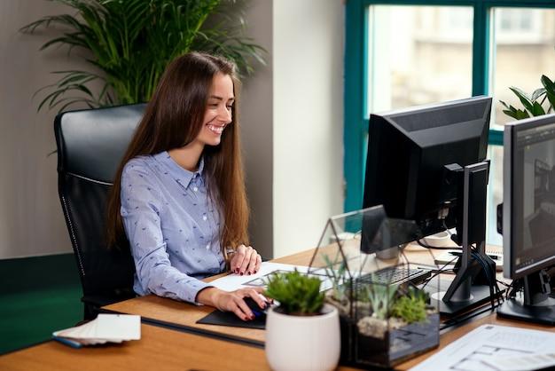 Привлекательный молодой женский архитектор в голубой рубашке, работающих в современном офисе.