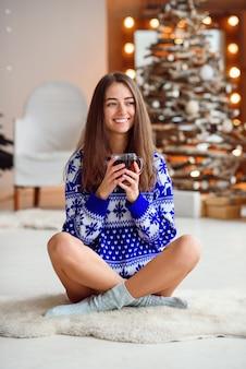Красивая улыбающаяся девушка в теплом новогоднем свитере сидит на тёплом белом ковре