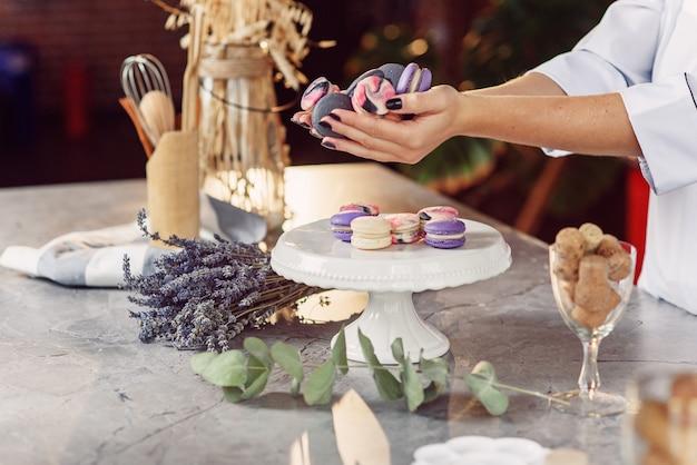 プレート、ラベンダー、ユーカリの大理石のテーブルの上にカラフルなフランスのマカロンを保持している黒のマニキュアで女性のパン屋の手を閉じます。