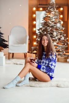 Привлекательная милая девушка в вязаном праздничном свитере сидит на теплом белом ковре с чашкой теплого чая