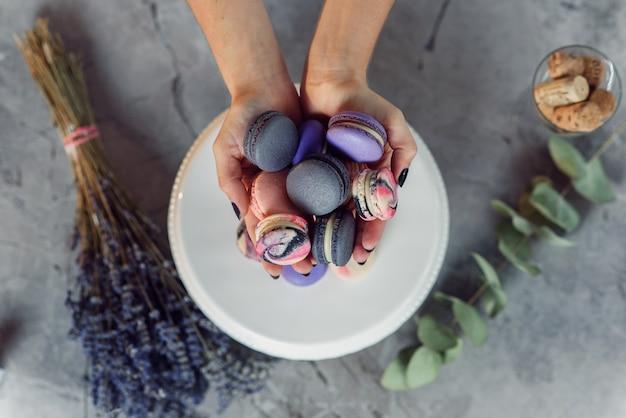 プレート、ラベンダー、ユーカリの大理石のテーブルの上にカラフルなフランスのマカロンを保持している黒のマニキュアで女性のパン屋の手を閉じます。上面図。