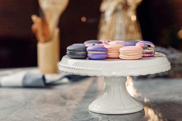 ナプキンとキッチンアクセサリーと大理石のテーブルの上の白いトレイに色のマカロン