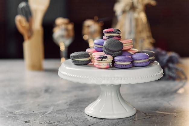 ナプキン、ラベンダー、キッチンアクセサリーと大理石のテーブルの白いトレイに色のマカロン。