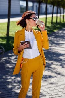 黄色のスーツとタブレットコンピューターとヘッドフォンとサングラスの美しいビジネス女性は、路地を歩きながらコーヒーを飲みます。
