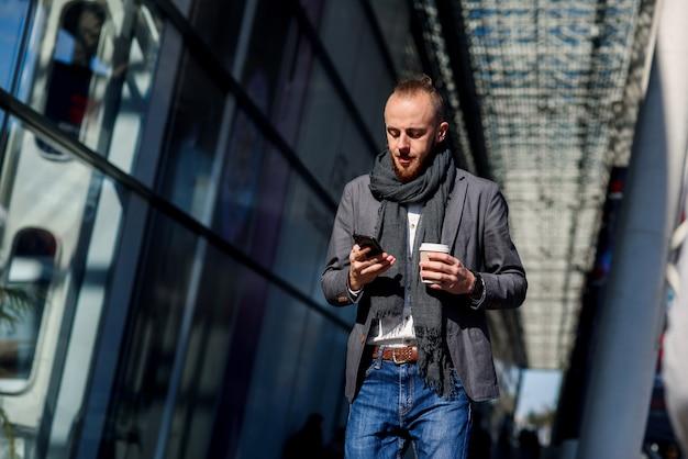 通りを歩いて、現代のスマートフォンを使用して、昼休み中にコーヒーを飲むメガネの青年実業家のクローズアップ。