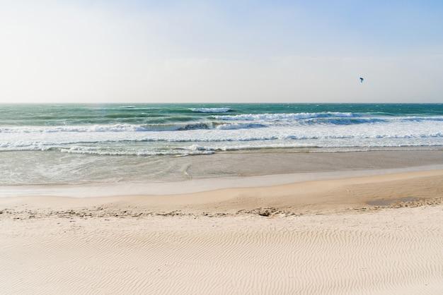 Песчаный берег моря с чистой водой и огромными волнами в море.