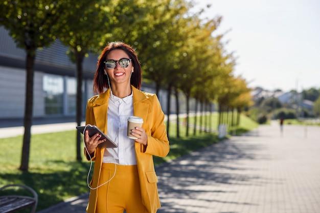 タブレットコンピューター、ヘッドフォン、コーヒーのカップを持つ若いビジネス女性の笑みを浮かべて路地を歩きます。