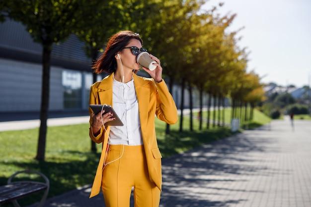 タブレットコンピューターとヘッドフォンと黄色のスーツを着たスタイリッシュなビジネス女性が路地を歩きながらコーヒーを飲みます。