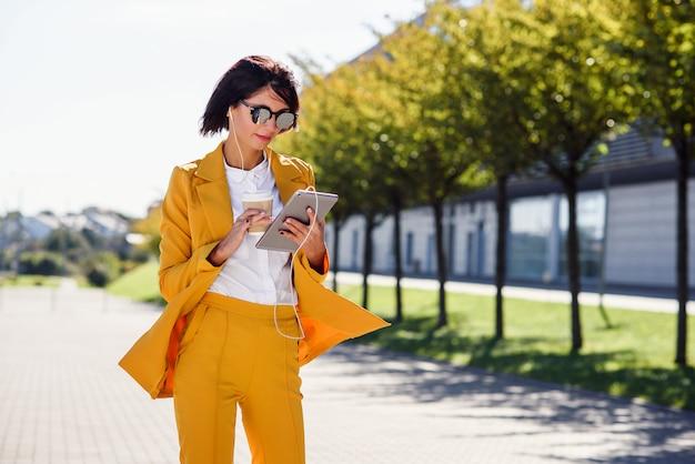 スタイリッシュな若いビジネス女性が一杯のコーヒーを散歩しながらタブレットコンピューターを使用してください。