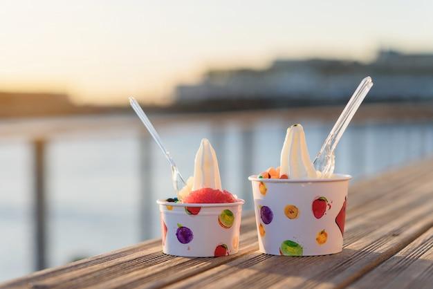 Две чашки мороженого с конфетами на закате.