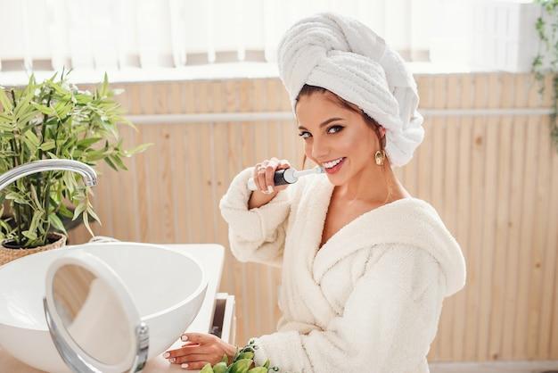 バスローブの魅力的な若い笑顔の女性が手に歯ブラシを保持し、カメラを見て