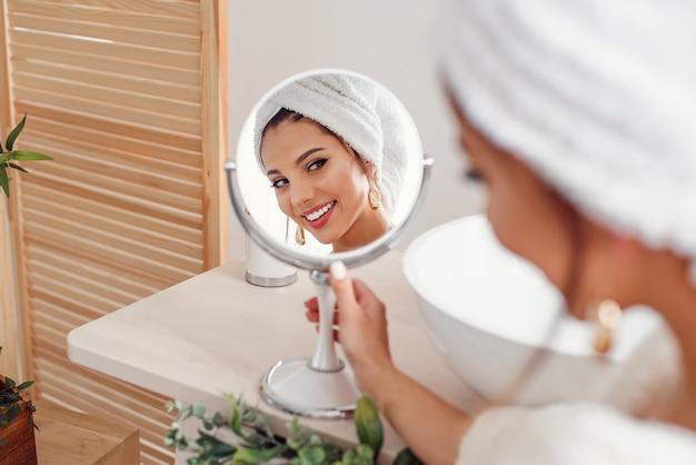 彼女の頭に白いタオルを持つ魅力的な若い女性は鏡で自分を見てください。