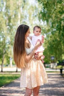 Молодая красивая мама с маленькой дочкой в руках, прогулки в парке.
