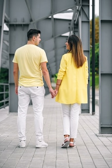 Прекрасная молодая пара в яркой одежде, держась за руки