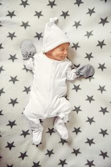 Спящий младенец в белой одежде и белой шляпе на пледе со звездами