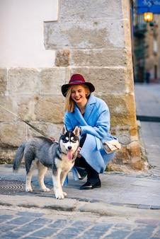 青いコートで幸せな笑顔と路上で若い犬犬種ハスキーとバーガンディの帽子を持つ若い幸せな観光女の子