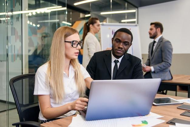 若い進歩的な会社のための将来の開発戦略を作成します。より良い会社の結果を得るための機会について議論している快適な高スキルのビジネスパーソン。