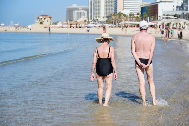 年配のカップルがビーチの上を歩きます。老人と恋の女性は海辺で休暇を過ごす。後ろからの眺め。