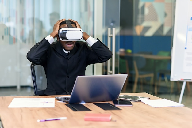Портрет молодой афроамериканец черный мужской профессионал с использованием голографической голограммы дополненной реальности в современном офисе