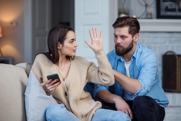 自宅でモダンなカップル。男性と女性はスマートフォンでのメッセージングに集中し、お互いを無視し、ソーシャルメディアに時間を費やしていました。