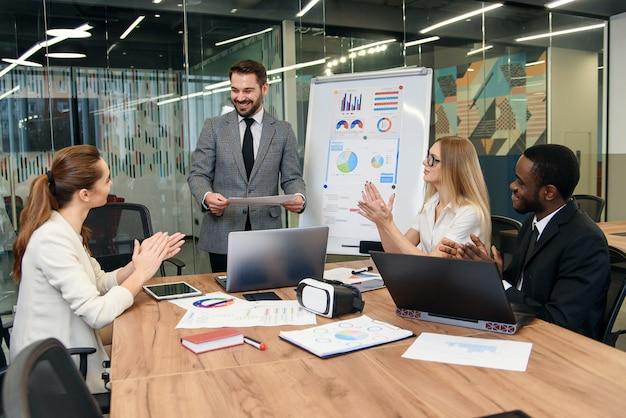 彼の気配りのあるビジネスグループに説明する見栄えの良い高スキルの男性ビジネスメンターは、女性と浅黒い肌の男性で構成され、共同プロジェクトでどのように連携するかを説明しています。