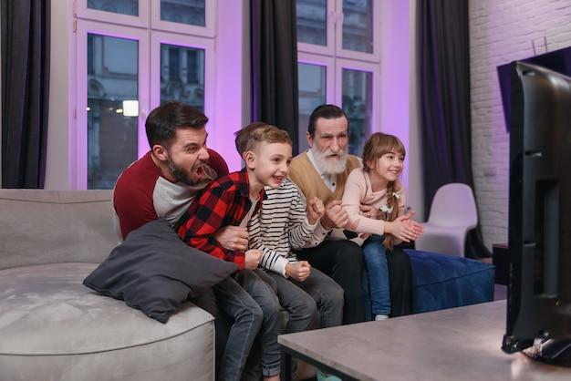 Семья смотрит американский футбольный матч, чемпионат на диване у себя дома. болельщики эмоционально болеют за любимую сборную. дети с отцом и дедушкой наслаждаются отдыхом дома.