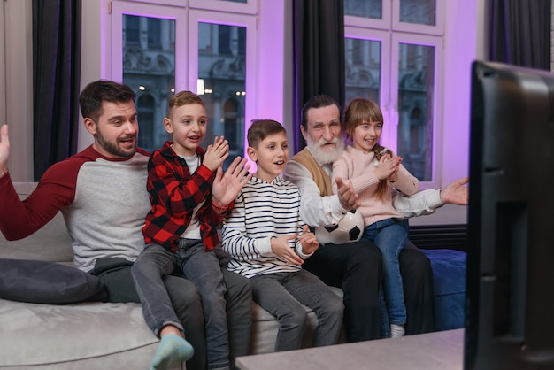Привлекательные три поколения людей, таких как отец, дедушка и внуки, сидят дома на удобном диване и наслаждаются досугом, наблюдая за футбольным матчем, крича, когда команда забивает мяч.