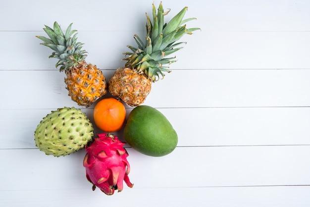 Экзотические свежие летние фрукты на белом. плод дракона, ананас, хурма, манго, анрона черимола плоская кладут со свободным пространством копии.