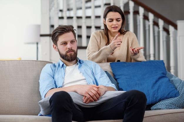 Смущенный мужчина сидит на диване, а его подруга кричит и ругается с ним дома. большие семейные проблемы.