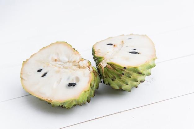 新鮮なエキゾチックなトロピカルフルーツ。白、アノナチェリモヤに分離されたカスタードアップルの半分。