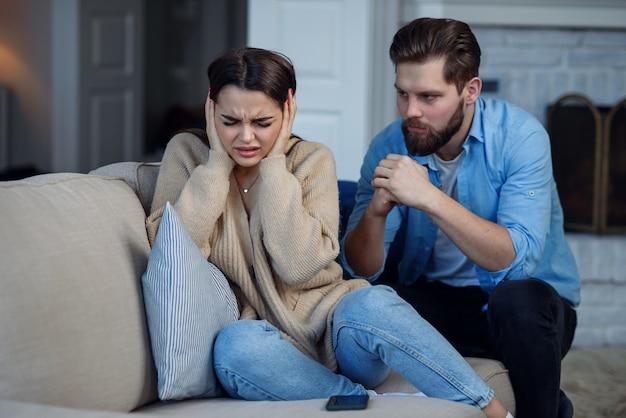Беззащитная расстроенная женщина закрывает уши, а муж кричит на нее, сидящую сзади. концепция проблемы семейных отношений.