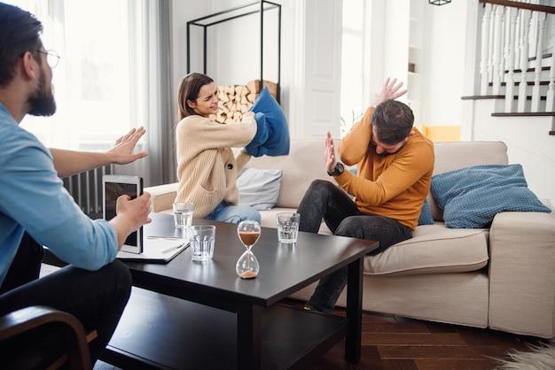 心理学者のオフィスで彼女のセラピーセッション中に彼女の怯えた夫を枕で打つ動揺の女性。