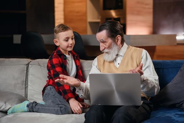 Внук учит своего деда пользоваться ноутбуком.